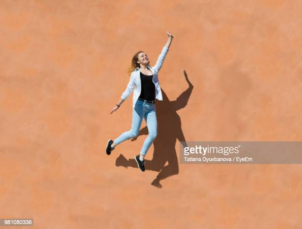 full length of young woman jumping by wall on sunny day - in de lucht zwevend stockfoto's en -beelden