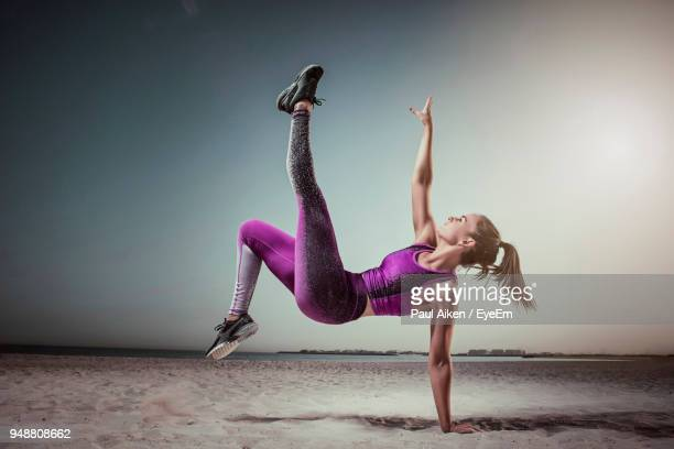 full length of young woman jumping on sand at beach - aikāne stock pictures, royalty-free photos & images