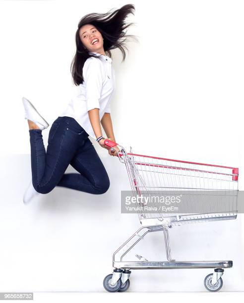full length of young woman jumping while holding shopping cart against white background - shopping cart stock pictures, royalty-free photos & images