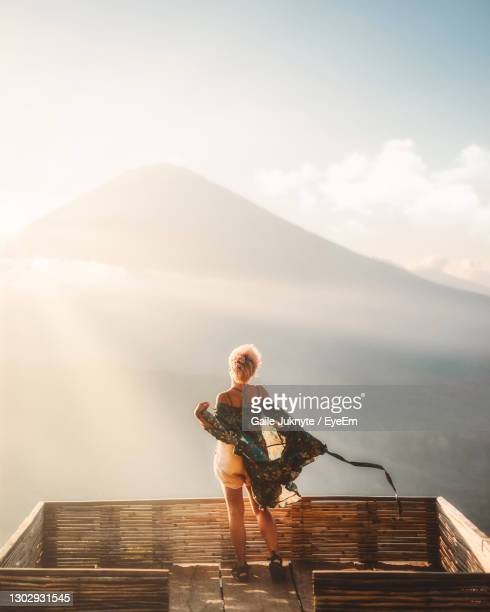 full length of young woman on pier against sky - golden hour stock pictures, royalty-free photos & images