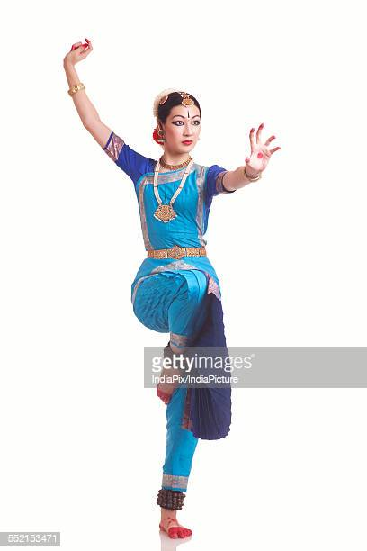 Full length of young woman performing classical dance on white background