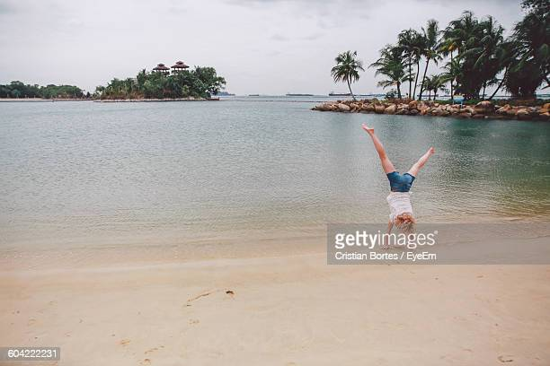 Full Length Of Young Woman Performing Handstand At Seashore