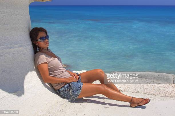 Full Length Of Young Woman Relaxing At Beach