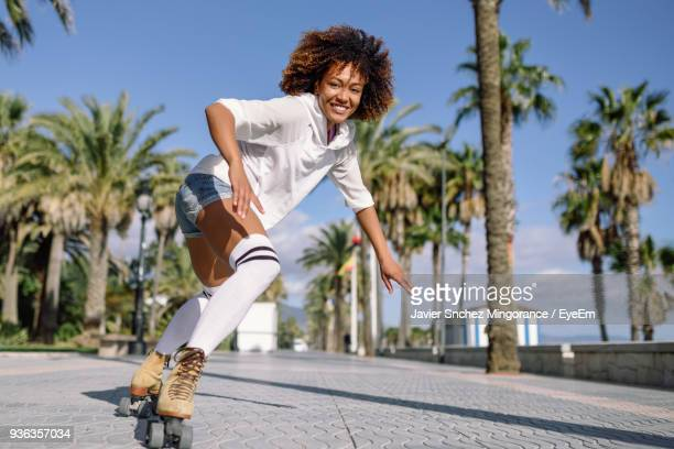 full length of young woman roller skating on street in city during sunny days - afro frisur stock-fotos und bilder