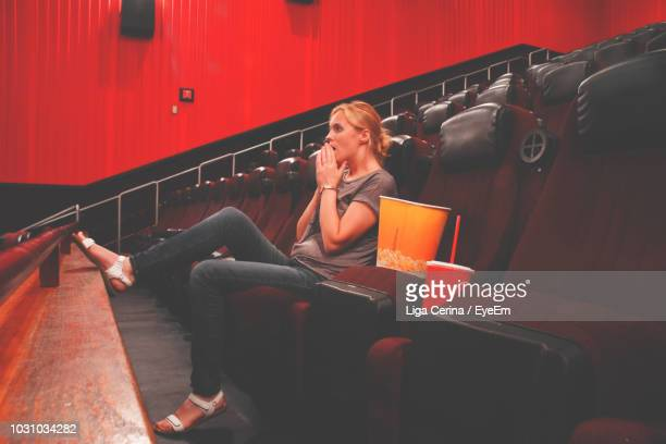 full length of young woman sitting at theatre - liga cerina stock pictures, royalty-free photos & images