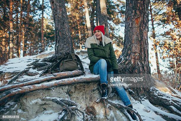 Full length of young woman sitting in snow covered forest