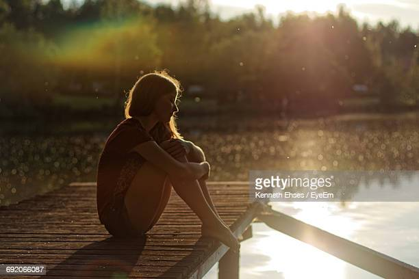 Full Length Of Young Woman Sitting On Pier During Sunset