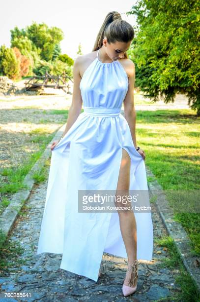 full length of young woman standing against tree - sleeveless dress stock photos and pictures