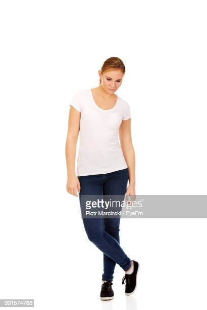 full length of young woman standing against white background - guardare verso il basso foto e immagini stock
