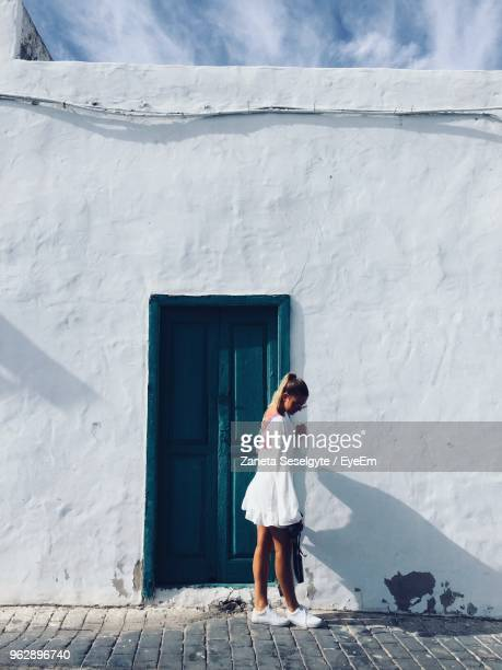 full length of young woman standing against whitewashed house - whitewashed stock photos and pictures