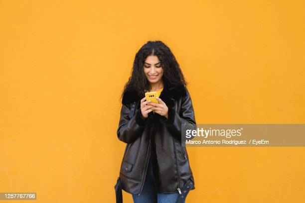 full length of young woman standing against yellow wall - jacket stock pictures, royalty-free photos & images