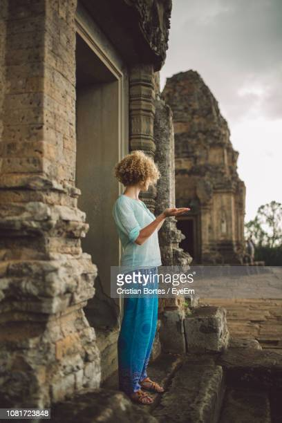 Full Length Of Young Woman Standing At Doorway Of Angkor Wat