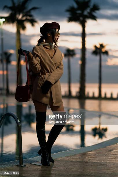 full length of young woman standing at poolside against sky during sunset - durazzo foto e immagini stock