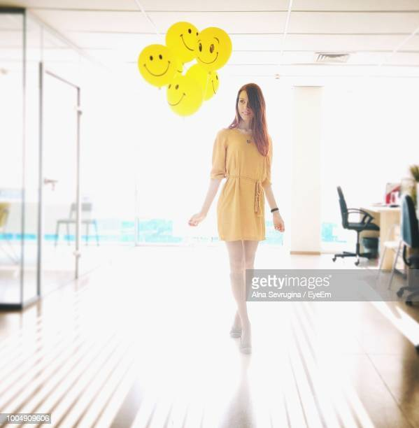 Full Length Of Young Woman Standing By Balloons In Office