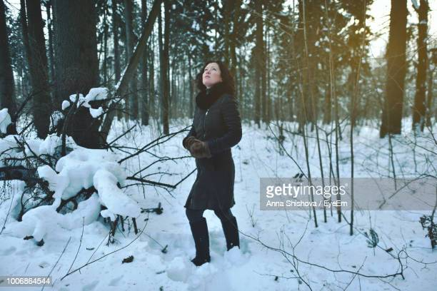 Full Length Of Young Woman Standing In Forest During Winter