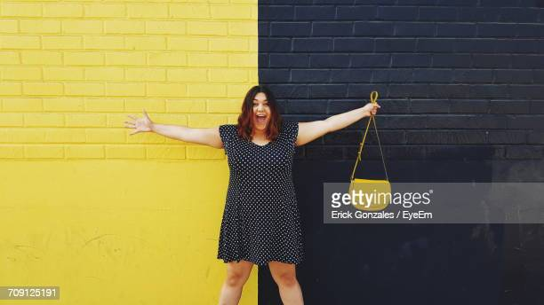 Full Length Of Young Woman Standing In Front Of Wall