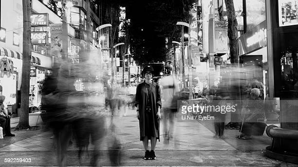 Full Length Of Young Woman Standing On Busy Street In City At Night