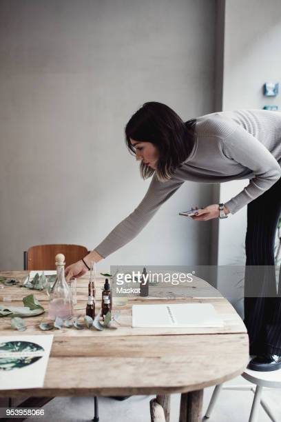 full length of young woman standing on chair arranging table at perfume workshop - bending over stock pictures, royalty-free photos & images
