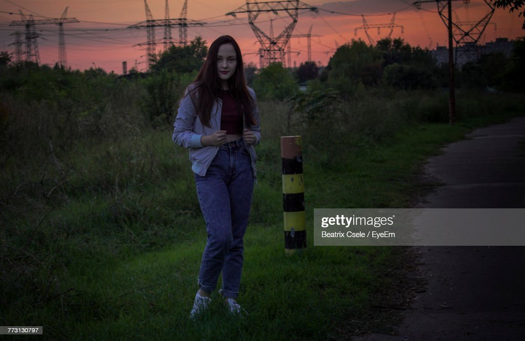 Full Length Of Young Woman Standing On Field During Sunset : Photo