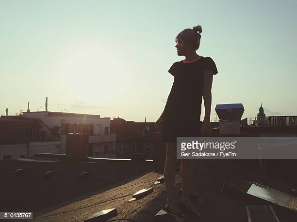 Full length of young woman standing on roof