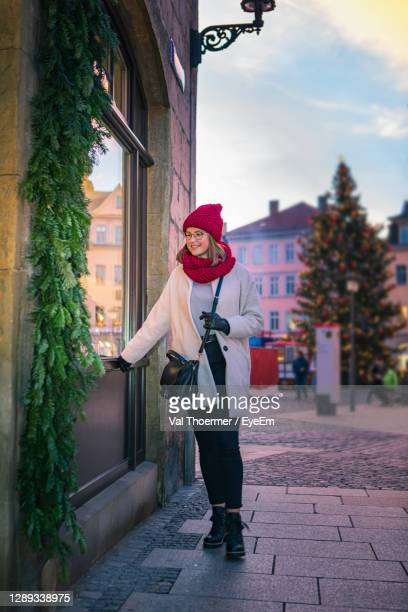 full length of young woman standing on street during winter - val thoermer stock-fotos und bilder