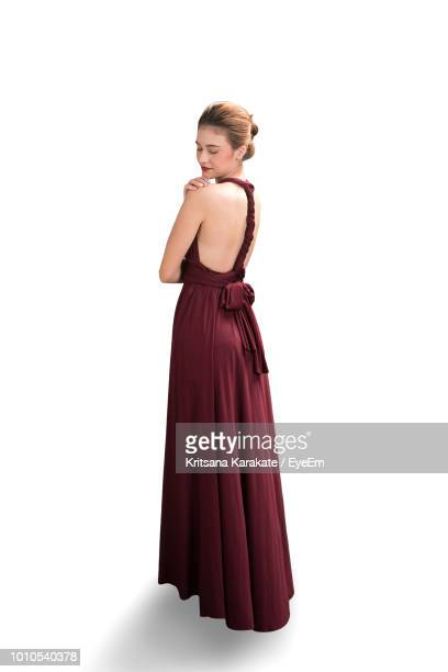 full length of young woman standing on white background - ロングドレス ストックフォトと画像