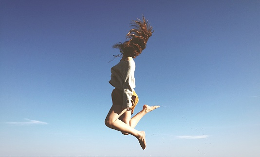 Full Length Of Young Woman Tossing Hair In Mid-Air Against Clear Blue Sky - gettyimageskorea