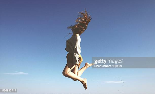 full length of young woman tossing hair in mid-air against clear blue sky - in de lucht zwevend stockfoto's en -beelden