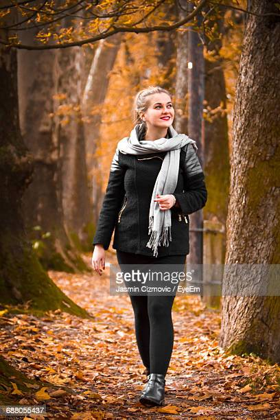 Full Length Of Young Woman Walking Along Autumn Trees