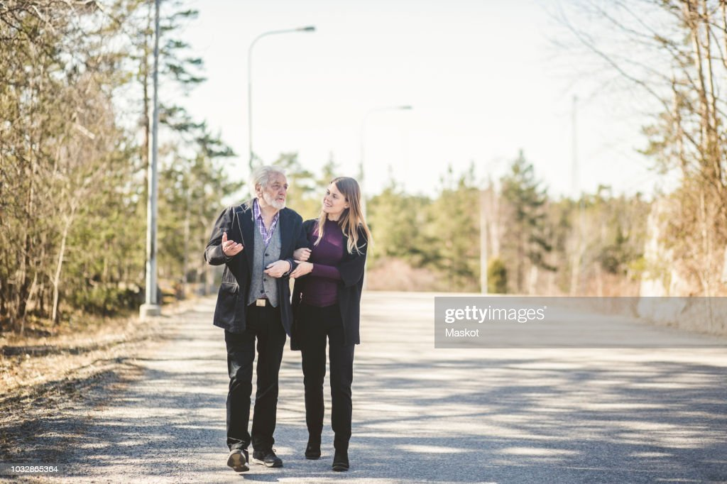 Full length of young woman walking arm in arm with grandfather on road : Stock Photo
