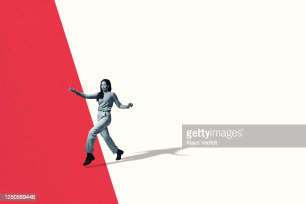 full length of young woman walking in stealth mode - verandering stockfoto's en -beelden