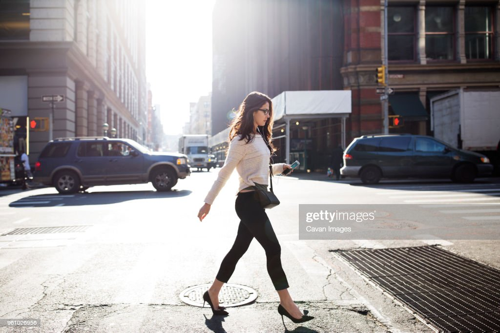 Full length of young woman walking on city street : Stock-Foto