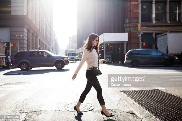 full length of young woman walking on city street - 横位置 ストックフォトと画像