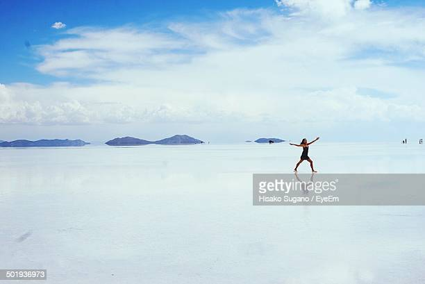 Full length of young woman walking on frozen lake