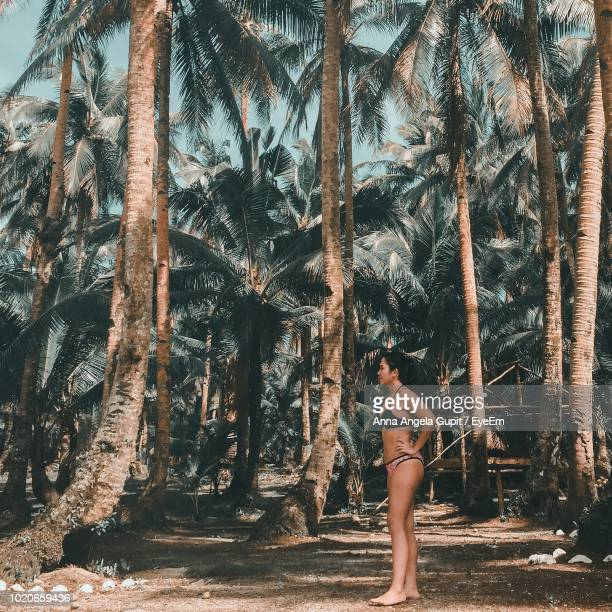 Full Length Of Young Woman Wearing Bikini While Standing In Forest