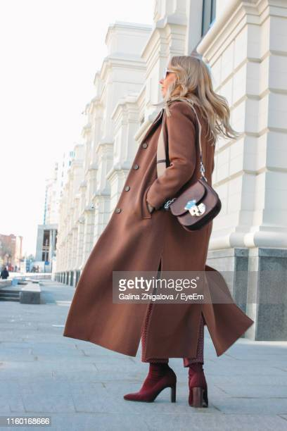 full length of young woman wearing long coat standing on sidewalk in city - long coat stock pictures, royalty-free photos & images