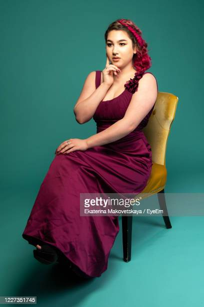 full length of young woman wearing maroon dress against green background - long dress stock pictures, royalty-free photos & images