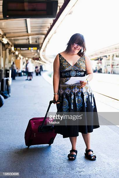Full length of young woman with down syndrome waiting with ticket at train platform