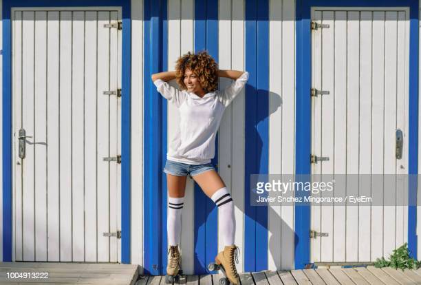 full length of young woman with frizzy hair standing against building - schwarze schuhe stock-fotos und bilder
