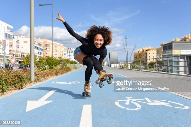 Full Length Of Young Woman With Roller Skates On Road Against Sky
