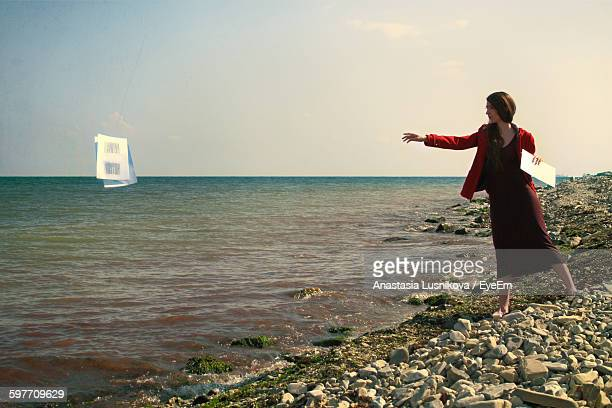 Full Length On Woman Throwing Papers In Sea