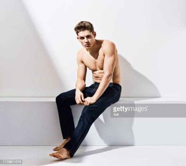 volle länge / ein mann nur von 20-29 jahre alt erwachsene stattliche menschen kaukasischen männlich / junge männer sitzen / ruhend vor weißem hintergrund tragen jeans, die ein sex-symbol ist / von muskelaufbau / shirtless / ernst / vertrauen / konzentr - halbbekleidet stock-fotos und bilder