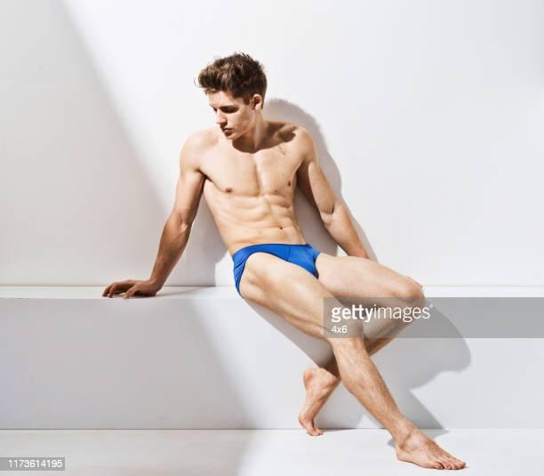 ●全長/20~29歳大人のハンサムな人のみ白人男性/若い男性/白い背景の前に座って下着/メンズパンツ/影のあるセミドレス - セミヌード ストックフォトと画像