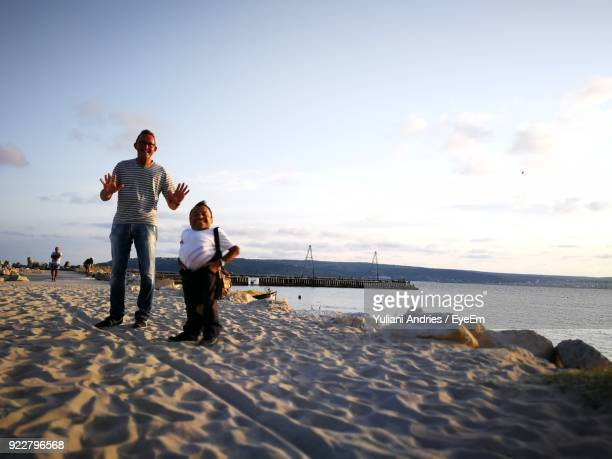 Full Length Of Man With Midget Friend Standing At Beach