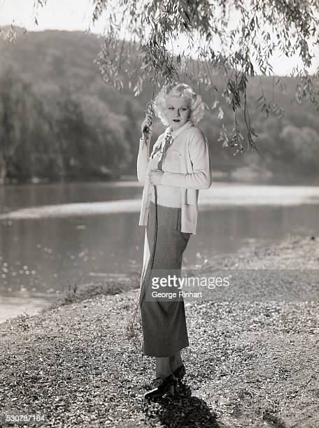Full Length photograph of the original 'Blonde Bombshell' actress Jean Harlow Harlow is outdoors standing by water and is holding a tree branch in...