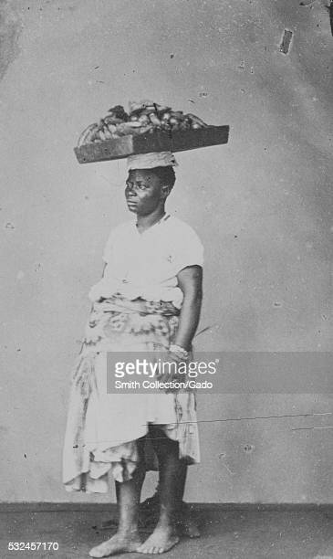 A full length photographic portrait of a woman with a wooden tray on her head the tray is full of bananas that the woman is taking to a market she...