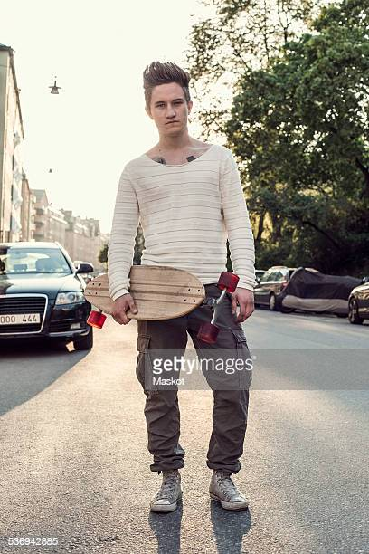 Full length portrait confident male high school student with skateboard standing on city street