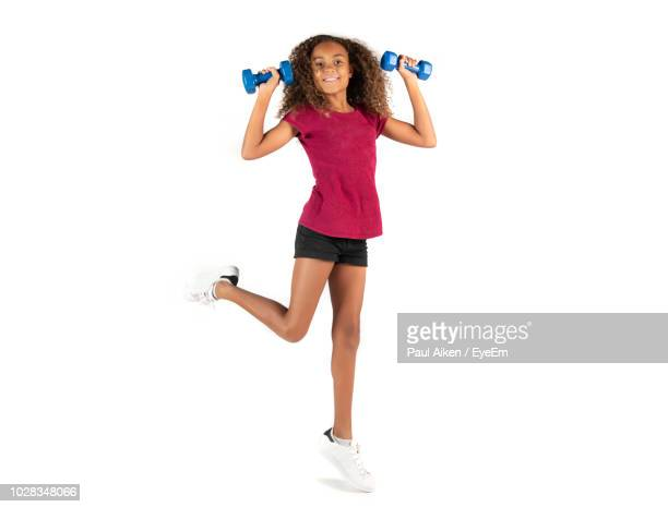 full length portrait girl lifting dumbbells against white background - aikāne stock pictures, royalty-free photos & images