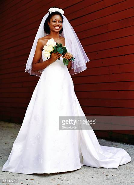 full length portrait of a bride holding a bouquet of white roses - velo foto e immagini stock
