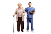 Full length portrait of a male nurse with a clipboard and an elderly female patient with a walking cane